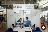 Am Stand von Ark Linux präsentieren Bero Rosenkränzer (rechts) und Kollegen Version Alpha 8 von Ark Linux. Auf dem rechten Monitor erkennt man das Videokonferenz-Tool, das auf GnomeMeeting basiert.