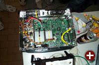 Eine geöffnete Xbox amerikanischer Bauart. Die Hardware-Modifikation ist links vom gelben Kabel zu erkennen.